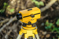 Yellow geodetic optical level on a tripod Royalty Free Stock Photo