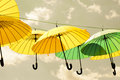 Yellow and green umbrellas hanging under a gray sky Royalty Free Stock Photo