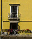Yellow house decorated balconies wall with gray shutters and with flowers in bolzano a town on the dolomites italy Royalty Free Stock Photos