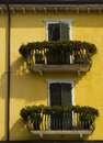 Yellow house green shutters decorated balconies wall with and with flowers in bardolino a town on the south east shores of lake Stock Photo