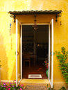 Yellow house wall with opened door and flower a Stock Photo