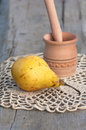 Yellow juicy pear and wood mortar on the crocheting lacy placemat Stock Photo