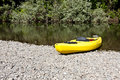 Yellow kayak rests on the river bank Royalty Free Stock Photo