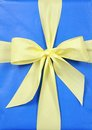 Yellow knot on blue gift box Royalty Free Stock Photo