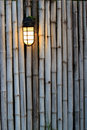 Yellow lamp on the bamboo fence Stock Image