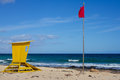 Yellow lifeguard tower. One life guard together red flag on beach. Point of safe, surviving. Coastal view. Royalty Free Stock Photo