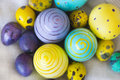 Yellow, light blue and violet Easter eggs with hand drawings of polka dots, butterflies and spirals Royalty Free Stock Photo