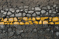 Yellow line on asphalt road crack surface Stock Images