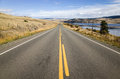 Yellow markings on a tarred highway leading straight off into the distance alongside lake in low hills in scenic landscape Stock Image