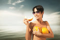 Yellow melons jesting picture of playful young woman in sunglasses with on sea background Stock Image