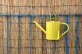 Yellow metal watering can, bamboo fence in background Royalty Free Stock Photo