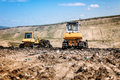 Yellow mini bulldozers working and moving garbage on dumping site Royalty Free Stock Photo