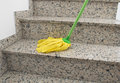 Yellow mop cleaning close up of stairs with Stock Photography