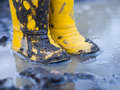 Yellow muddy boots puddle Stock Images