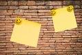 Yellow note pad on brick wall Royalty Free Stock Photo