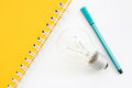 Yellow notebook with green pencil and lightblub Royalty Free Stock Photo