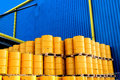 Yellow oil drums in front of a factory with blue cladding Royalty Free Stock Photo