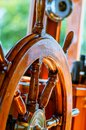 Yellow, old, lacquered, wooden steering wheel on a marine yacht Royalty Free Stock Photo