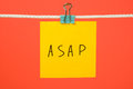 Yellow paper note on the string with text ASAP Royalty Free Stock Photo