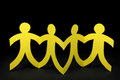 Yellow paper people on black background row of Stock Images