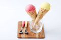 Yellow passion fruit and red strawberry ice cream cones Royalty Free Stock Photo