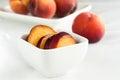 Yellow peaches in white square bowl Royalty Free Stock Photo