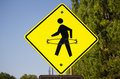 A yellow pedestrian crosswalk sign with a hula hoop drawn onto it. Royalty Free Stock Photo