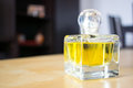 Yellow perfume bottle standing on table Stock Image