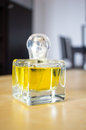 Yellow perfume bottle standing on table Stock Photography
