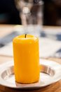 Yellow perfumed candle on the table Royalty Free Stock Photography