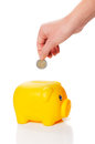 Yellow piggy bank is getting two euro coin from a hand Royalty Free Stock Photo
