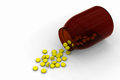 Yellow pills spilled from a bottle Royalty Free Stock Images