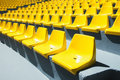 Yellow plastic chairs in a row Royalty Free Stock Photo