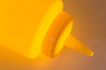 Yellow plastic mustard bottle clloseup with a glowing light Royalty Free Stock Photo
