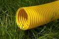 Yellow plastic pipe on green grass Royalty Free Stock Photo