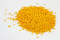Yellow plastic polymer granules on white background Stock Photos