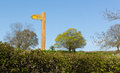 Yellow public footpath sign on wooden post with hedge trees and blue sky Royalty Free Stock Photo