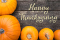 Yellow Pumpkins on a wooden table, Text Happy Thanksgiving, Flat