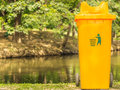 Yellow recycle bin in park Stock Photo
