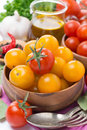 Yellow and red cherry tomatoes in wooden bowl olive oil spices close up vertical Stock Photos