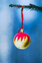 Yellow and red decoration ball dangles on the christmas tree closeup view of a which a ribbon canvas texture was added to Royalty Free Stock Photography