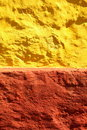 Yellow red paint wall background or texture close up uneven rough old concrete stone Stock Image