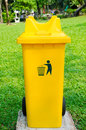 Yellow refuse bin in park plastic green Royalty Free Stock Photography