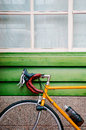 Yellow Road bicycles parking against green wooden wall. Royalty Free Stock Photo