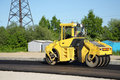 Yellow rolling machinery paving a road at summer Royalty Free Stock Photos