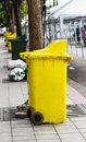 Yellow rubbish bin on footpath thailand Stock Photo