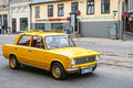 Yellow russian soviet car driving on the city street