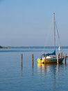Yellow sailboat moored to pier waiting s owner Stock Photography