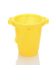 Yellow sand bucket on white closeup of a over a background with reflection Royalty Free Stock Photos