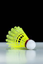 Yellow shuttlecock on white table with black background Stock Photos